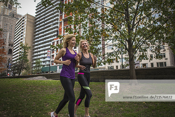 Two mature female friends running together in park