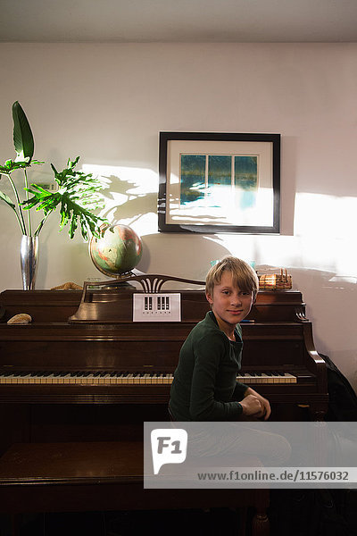 Portrait of boy sitting at piano in living room