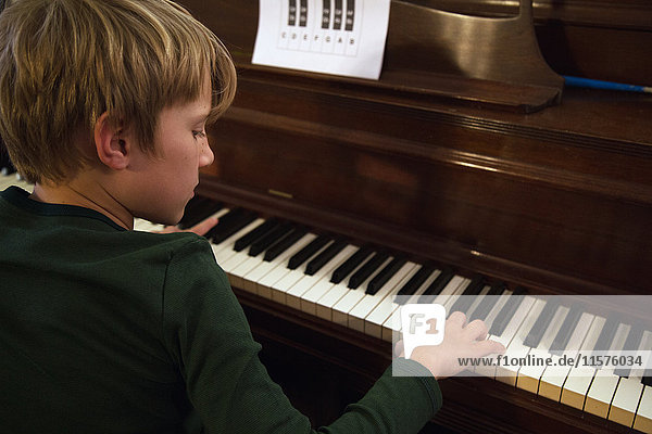 Over shoulder view of boy playing piano in living room