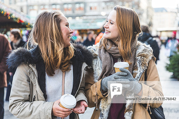 Two young female friends having takeaway coffee at christmas market