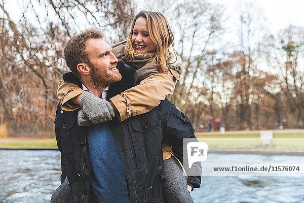 Junge Frau wird am Flussufer des Parks von ihrem Freund huckepack genommen