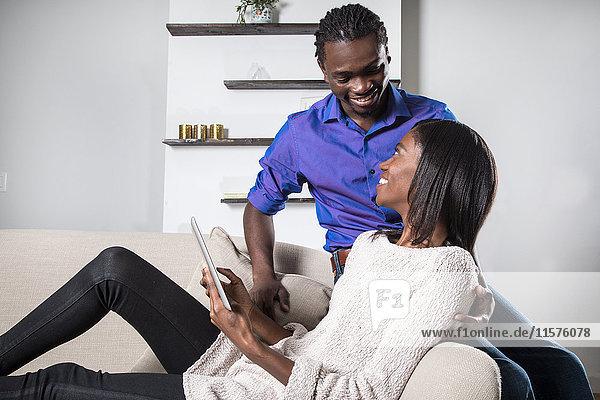 Junges Paar entspannt sich auf dem Sofa und schaut sich das digitale Tablett an.