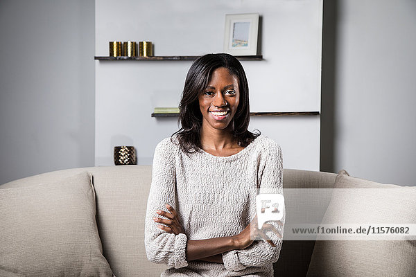 Porträt einer jungen Frau auf dem Sofa sitzend  lächelnd