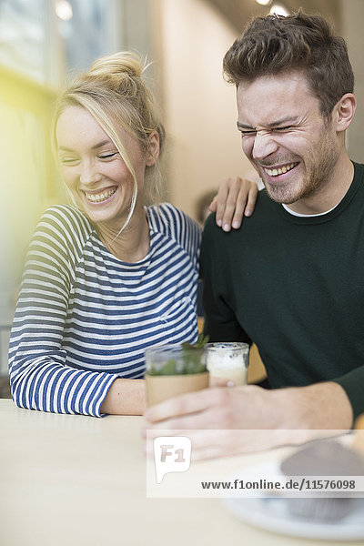 Couple sitting laughing together in cafe