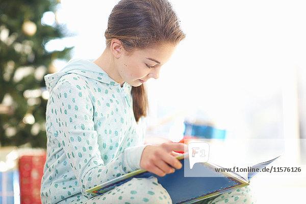 Girl sitting on living room floor reading book at christmas