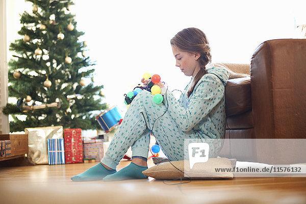 Girl sitting on living room floor untangling christmas lights at christmas