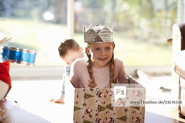 Girl sitting in cardboard box at christmas