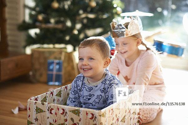 Girl pushing brother in cardboard box at christmas