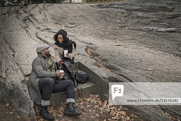 Ehepaar sitzt auf einer Treppe im Park mit Kaffee zum Mitnehmen