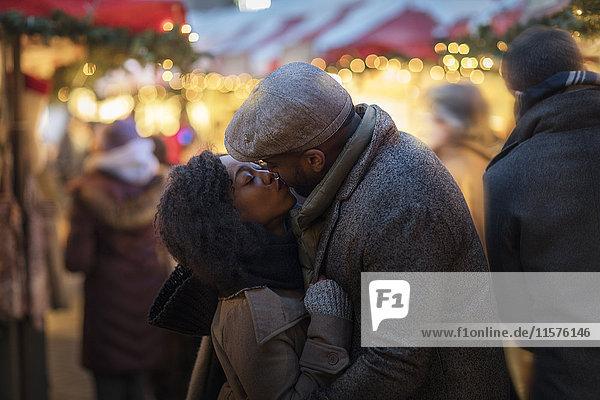Romantisches Paar küsst sich auf dem Weihnachtsmarkt  New York  USA
