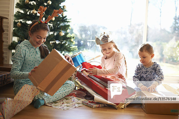 Boy and sisters sitting on living room floor opening christmas gifts