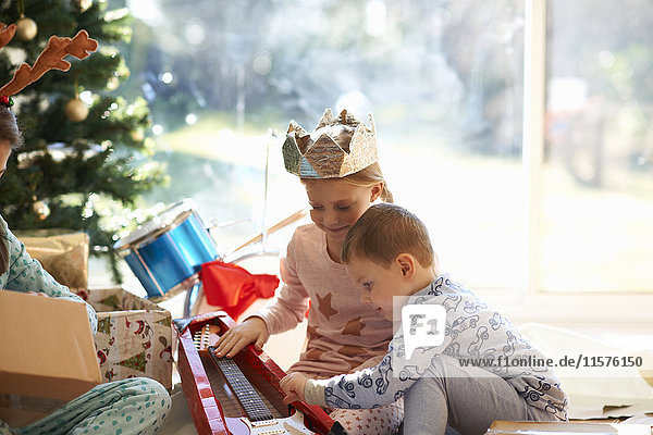 Girl and brother on living room floor looking at toy guitar christmas gift