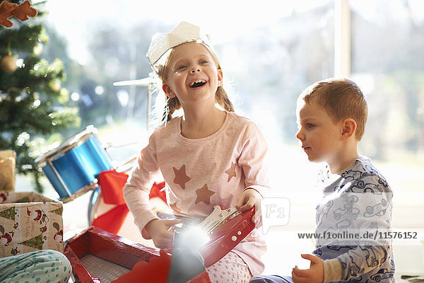 Excited girl and brother on living room floor with toy guitar christmas gift