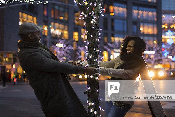 Couple holding hands around illuminated tree at night  New York  USA