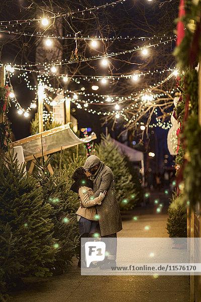Romantisches Paar küsst sich nachts auf dem Weihnachtsmarkt  New York  USA