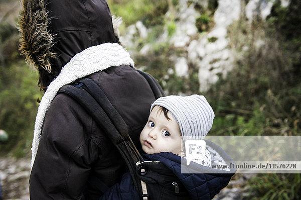 Porträt eines kleinen Jungen mit Strickmütze  von der Mutter im Tragetuch getragen