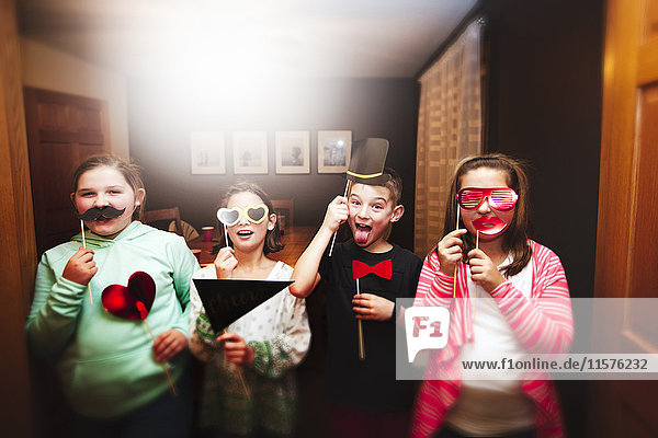 Portrait of boy and three girls holding sunglasses and mustache stick masks at party