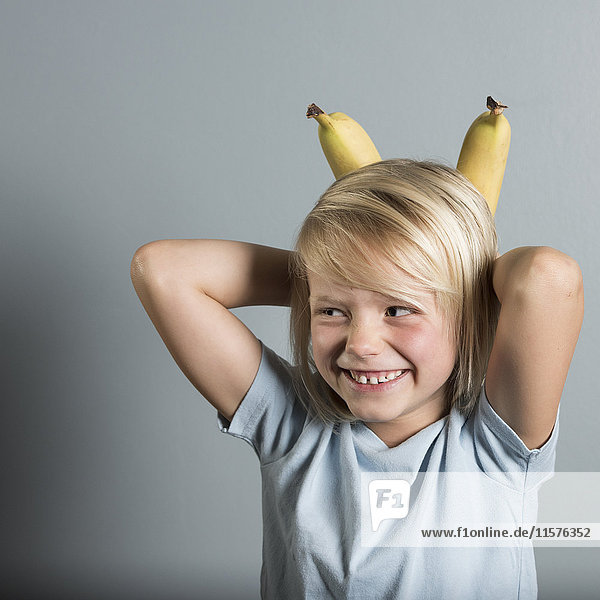 Portrait of boy with hands behind head holding bananas