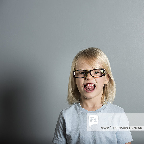 Portrait of boy wearing glasses sticking out tongue