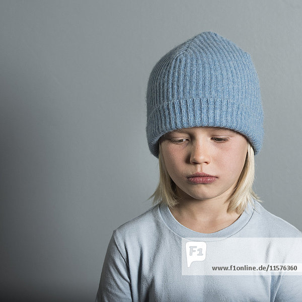 Portrait of boy wearing wool hat looking sad