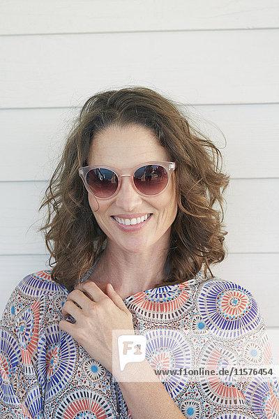 Porträt einer Frau mit Sonnenbrille  die lächelnd in die Kamera schaut