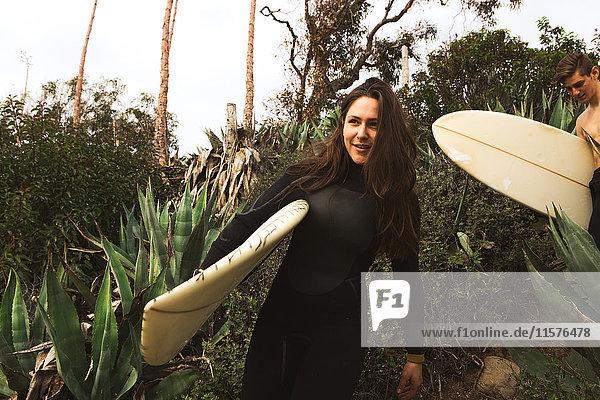 Freunde gehen in Richtung Strand  tragen Surfbretter