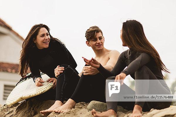 Drei Freunde sitzen am Strand und unterhalten sich