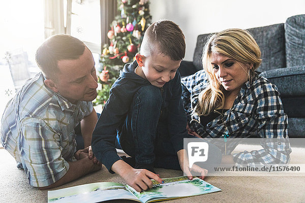 Mother and father listening to son read book