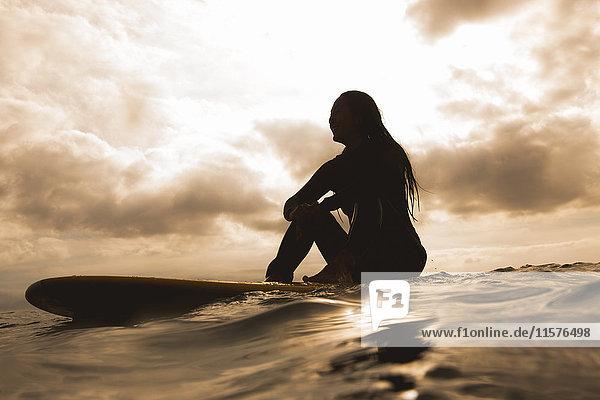 Junge Frau im Meer  auf einem Surfbrett sitzend