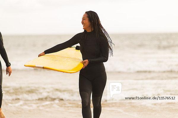 Freunde gehen vom Meer weg  tragen Surfbretter