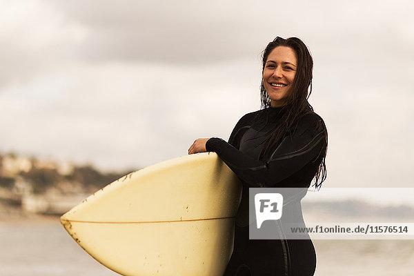 Junge Frau  die vom Meer weggeht und Surfbretter trägt