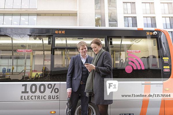 Fahrgäste  die ein Smartphone benutzen  um sich vor dem Einsteigen in den Elektrobus den Busfahrplan anzusehen
