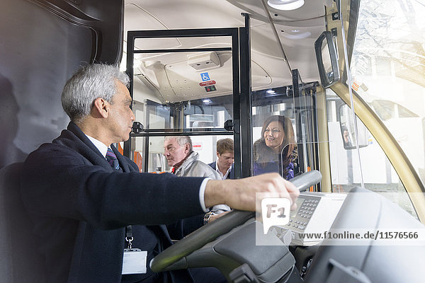 Busfahrer mit Fahrgästen beim Einsteigen in den Elektrobus