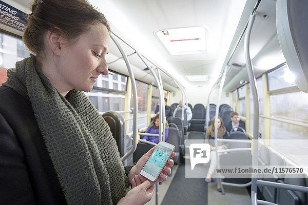 Fahrgast nutzt Smartphone zur Kartenabfrage im Elektrobus