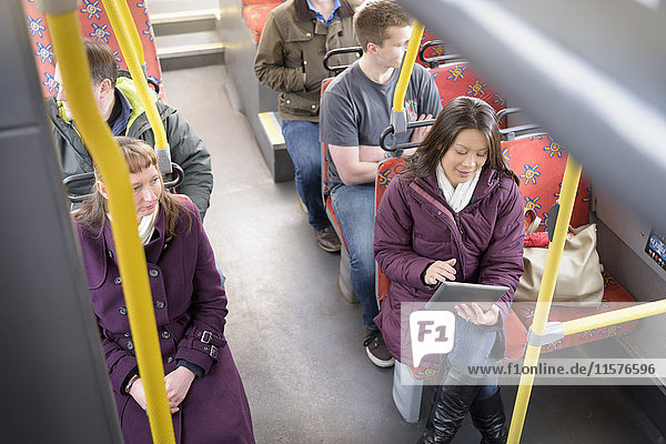 Passenger using digital tablet on electric bus  high angle view