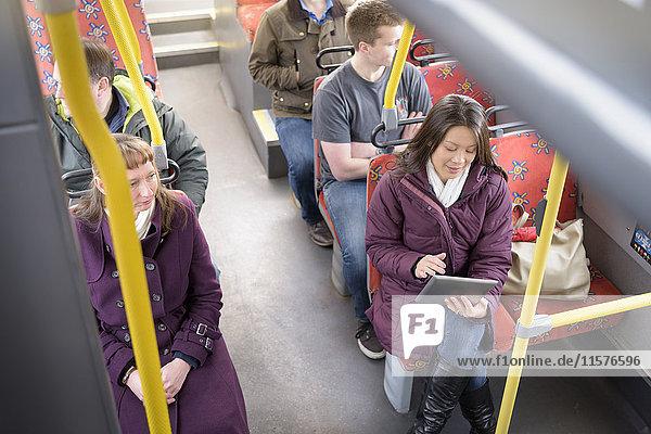 Fahrgast mit digitalem Tablet im Elektrobus  Hochwinkelansicht