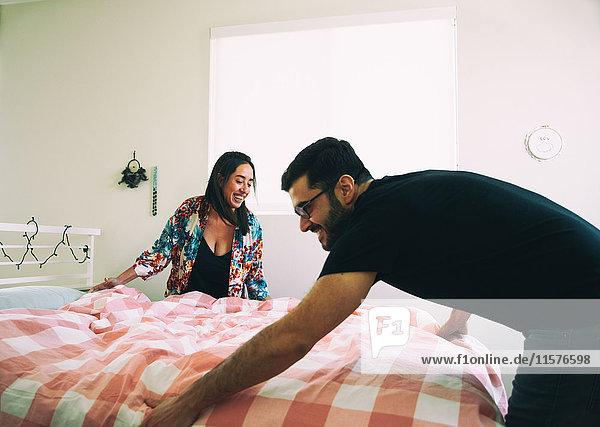 Glückliches Paar macht gemeinsam das Bett
