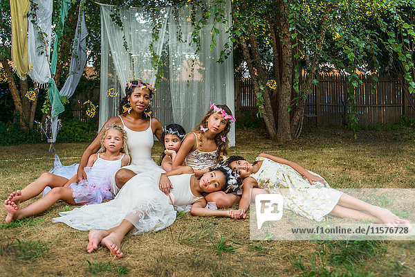 Portrait of mature woman with group of young girls  dressed as fairies  outdoors