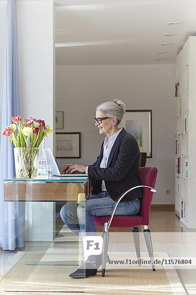 Leitende Geschäftsfrau tippt am Laptop am heimischen Schreibtisch
