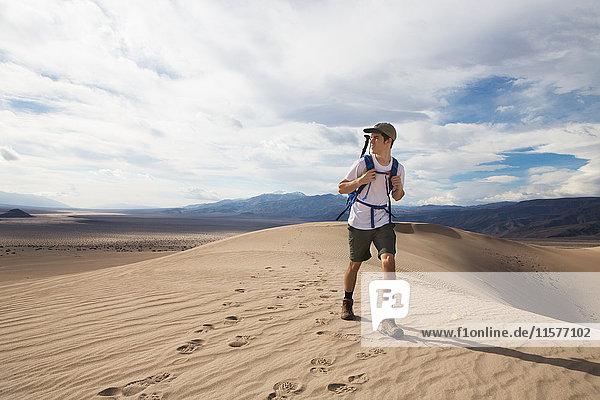 Trekker running in Death Valley National Park  California  US