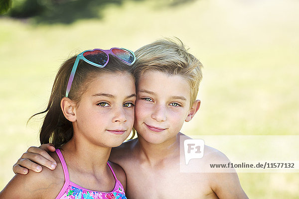 Summer portrait of boy with arm around twin sister