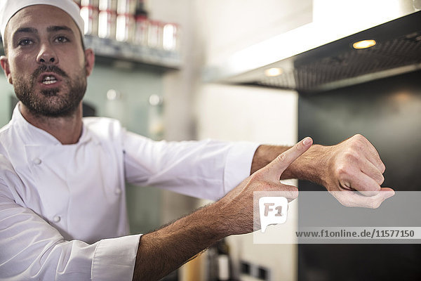 Chef signalling time by putting finger on wrist