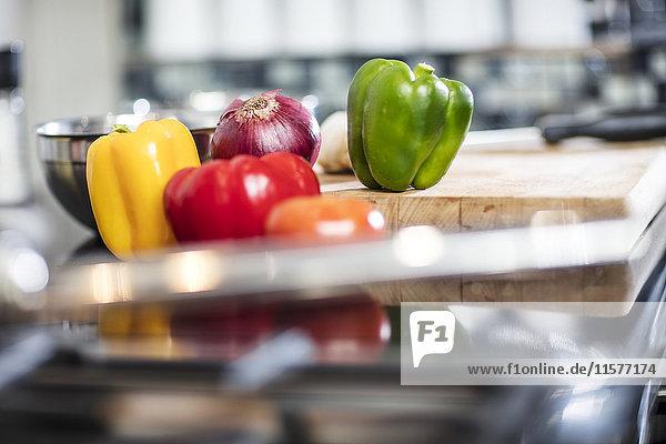 Stilleben von frischem Paprika und roter Zwiebel auf dem Schneidebrett in der Küche  Nahaufnahme