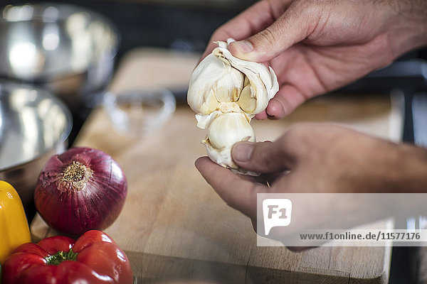 Chefkoch beim Schälen von frischem Knoblauch  Nahaufnahme