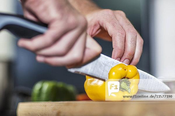 Koch schneidet gelbe Paprika in Scheiben  Nahaufnahme