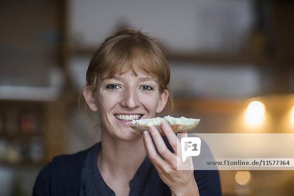 Junge Frau isst Brot mit Frischkäse