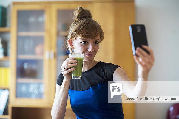 Junge Frau hält Smoothie in der Hand  nimmt Selfie mit Smartphone