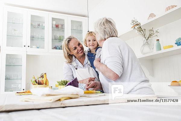 Ältere Frau  Tochter und Enkelin bereiten Gemüse am Küchentisch zu