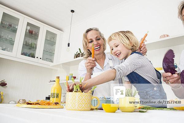 Mädchen und Mutter bereiten Karotten am Küchentisch zu