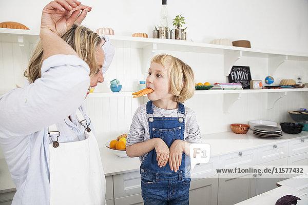 Reife Frau und Tochter imitieren Kaninchen mit Karotten in der Küche